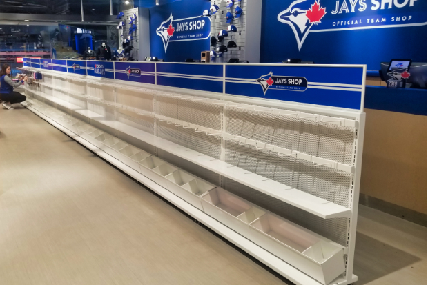 An employee adds products to empty shelves in Jays Shop
